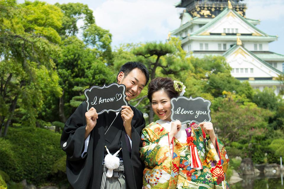 大阪城をバックに「I love you」「I know」のプレートを持ったお二人