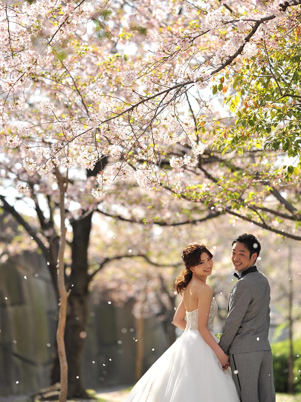 桜の木の下でドレスとタキシードをお召しになりほほえむお二人