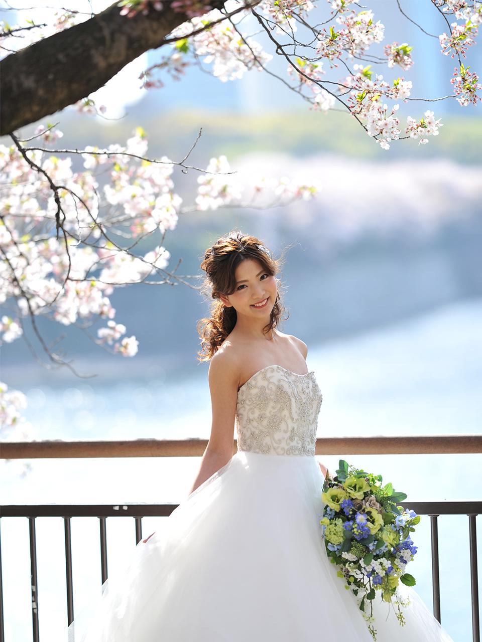 桜の木の下でウェディングドレスをお召しになりほほえむ花嫁