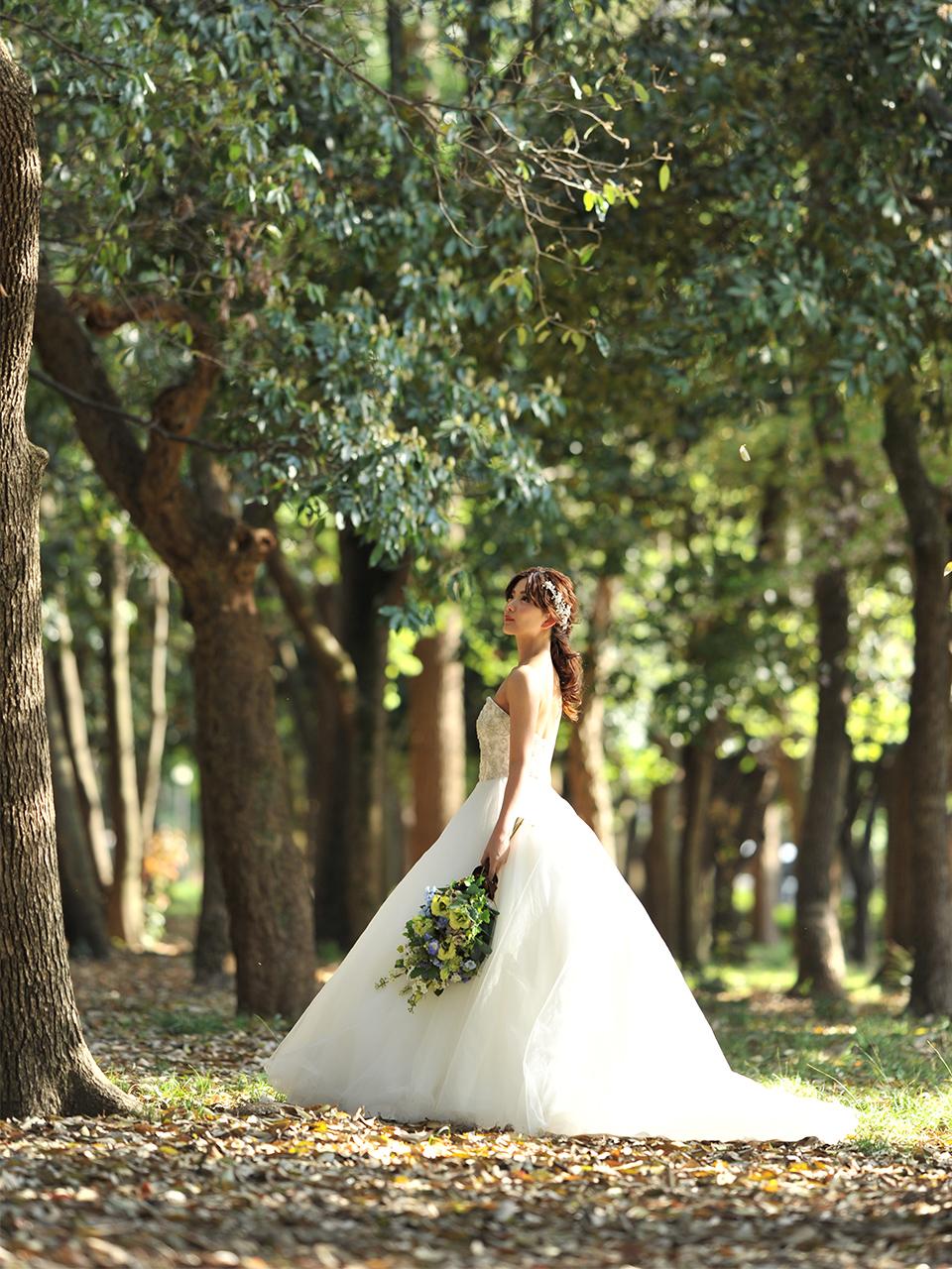 木の下でウェディングドレスでたたずむ花嫁