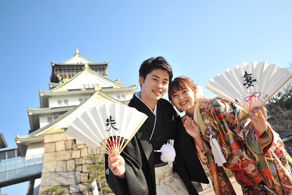 大阪城をバックに「夫」「妻」の扇子を持ったお二人