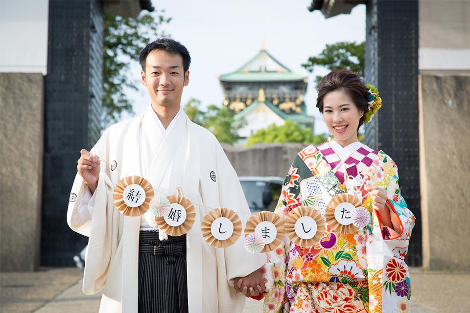 大阪城をバックに「結婚しました」のフォトプロップスを持ったお二人