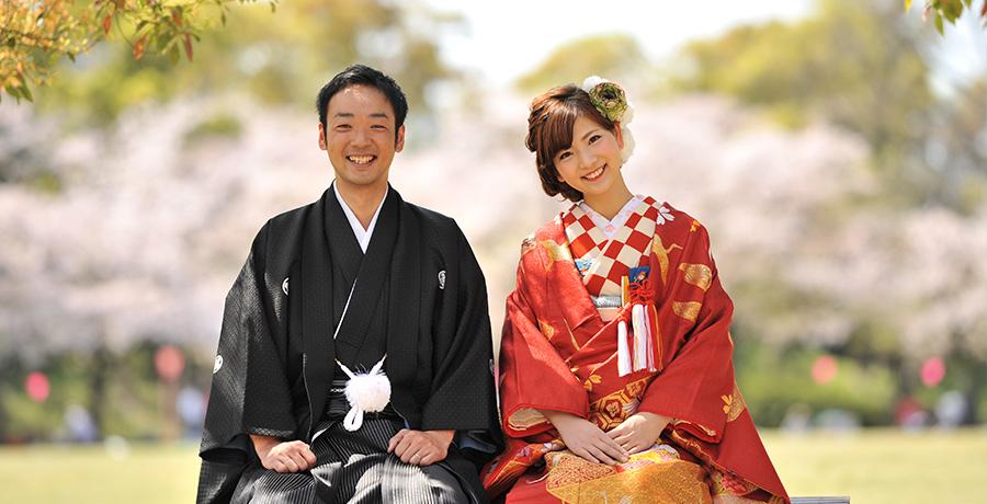 大阪城公園内桜をバックに座るお二方のお写真